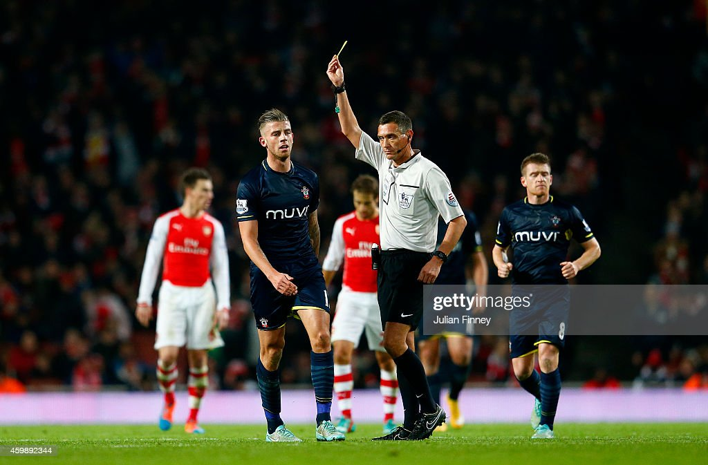 Toby Alderweireld of Southampton receives a yellow card from referee Andre Marriner after fouling Alexis Sanchez of Arsenal during the Barclays...