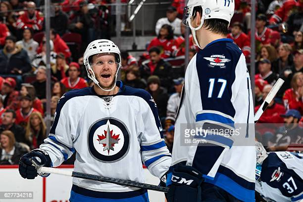 Toby Enstrom and Adam Lowry talk in the third period against the Chicago Blackhawks at the United Center on December 4 2016 in Chicago Illinois