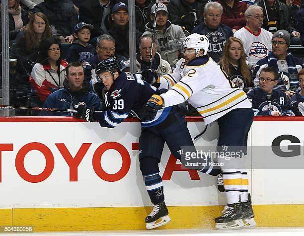 Toby Enstrom of the Winnipeg Jets gets checked into the boards by Marcus Foligno of the Buffalo Sabres during first period action at the MTS Centre...