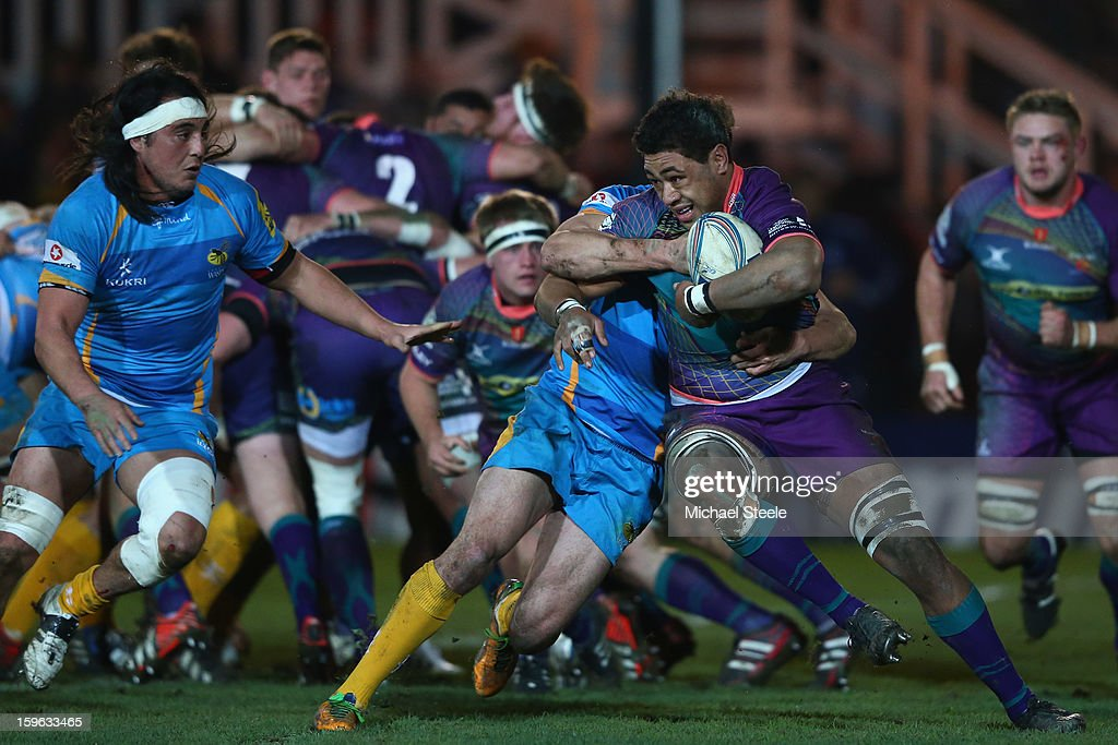 Toby Faletau (R) of Newport Gwent Dragons is held up by Charlie Davies of London Wasps as Jonathan Poff (L) closes in during the Amlin Challenge Cup Pool Three match between Newport Gwent Dragons and London Wasps at Rodney Parade on January 17, 2013 in Newport, Wales.