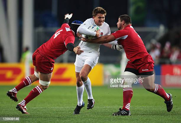 Toby Flood of England is tackled by Ilia Zedginidze and David Kubriashvili of Georgia during the IRB 2011 Rugby World Cup Pool B match between...