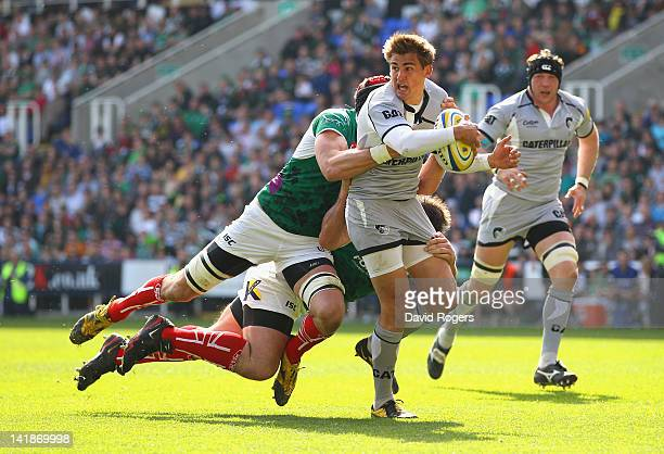 Toby Flood of Leicester breaks away from the tackle from Nick Kennedy and Faan Rautenbach during the Aviva Premiership match between London Irish and...