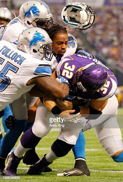Toby Gerhart of the Minnesota Vikings runs against Detroit Lions players Stephen Tulloch Joique Bell and Jonte Green whose helmet flies off on the...