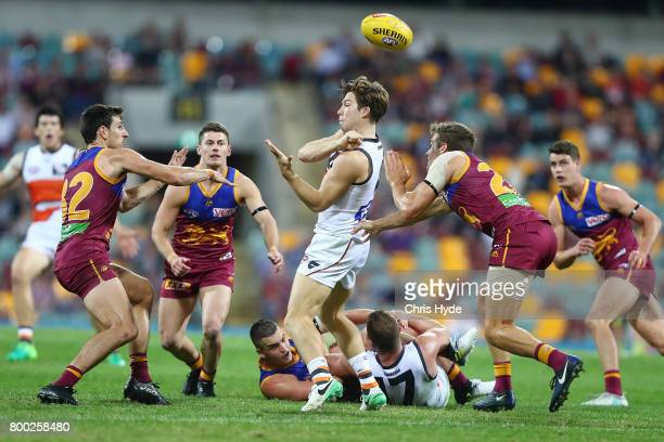 Toby Greene of the Giants handballs during the round 14 AFL match between the Brisbane Lions and the Greater Western Sydney Giants at The Gabba on...
