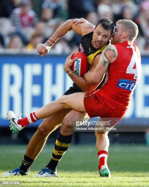 Toby Nankervis of the Tigers is tackled by Dan Hannebery of the Swans during the 2017 AFL round 13 match between the Richmond Tigers and the Sydney...
