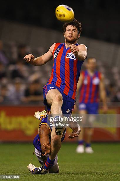 Toby Pinwill of Port Melbourne kicks whilst being tackled during the VFL Grand Final match between Port Melbourne and Williamstown at Etihad Stadium...