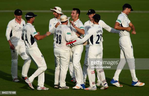 Toby RolandJones of Middlesex celebrates with his teammates after dismissing Rory Burns of Surrey during day one of the Specsavers County...