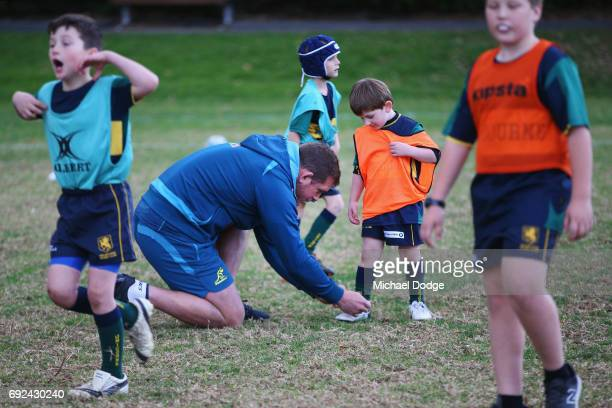 Toby Smith of the Wallabies ties up a young fans shoe lace during an Australian Wallabies training session at the Melbourne Rugby Union Football Club...