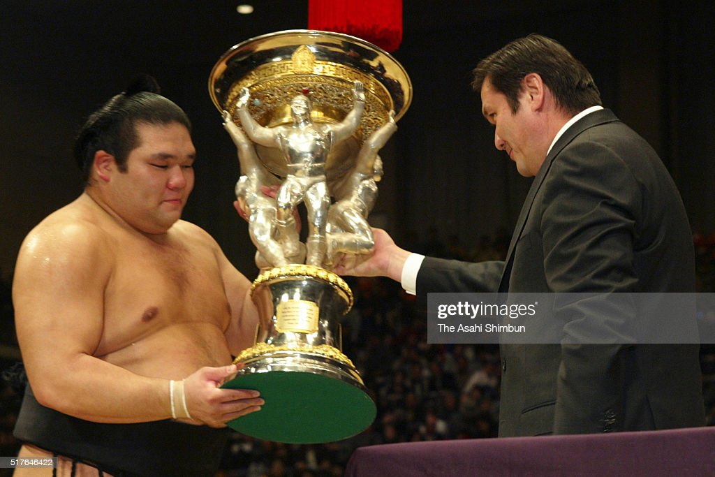 Tochiazuma receives the trophy from Mongolian Prime Minister Nambaryn Enkhbayar after winning the tournament during day fifteen of the Grand Sumo...