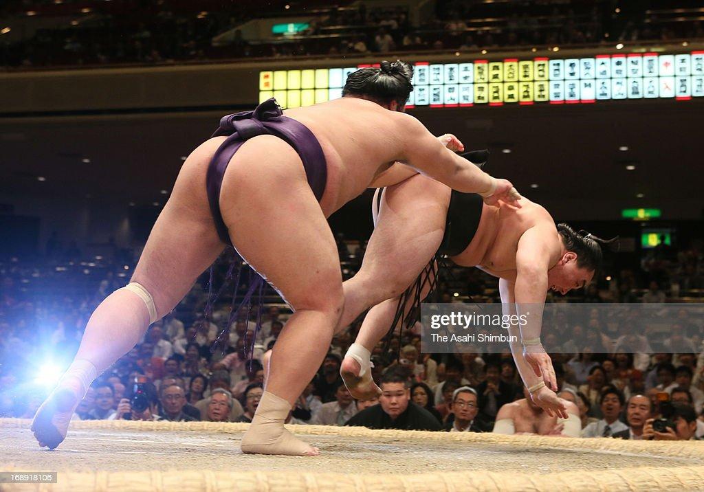 Tochiozan (L) throws Mongolian yokozuna Harumafuji, whose real name is Davaanyamyn Byambadorj during day five of the Grand Sumo Summer tournament at Ryogoku Kokugikan on May 16, 2013 in Tokyo, Japan.