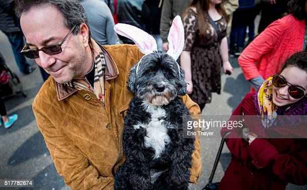 Todd Auslinder holds his dog Heidi during the Easter Parade and Bonnet Festival along 5th Avenue March 27 2016 in New York City The parade is a New...