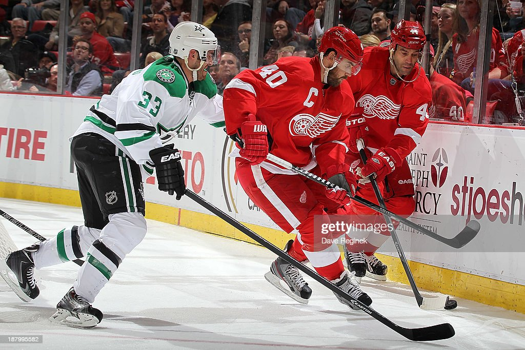 Todd Bertuzzi #44 and Henrik Zetterberg #40 of the Detroit Red Wings protect the puck from Alex Goligoski #33 of the Dallas Stars during an NHL game at Joe Louis Arena on November 7, 2013 in Detroit, Michigan. Dallas defeated Detroit 4-3 in OT.