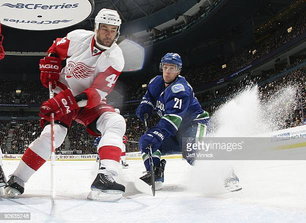 Todd Bertuzzi of the Detroit Red Wings and Mason Raymond of the Vancouver Canucks look for a rebound during their game at General Motors Place on...