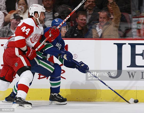 Todd Bertuzzi of the Detroit Red Wings and Mason Raymond of the Vancouver Canucks battle along the boards during their game at General Motors Place...