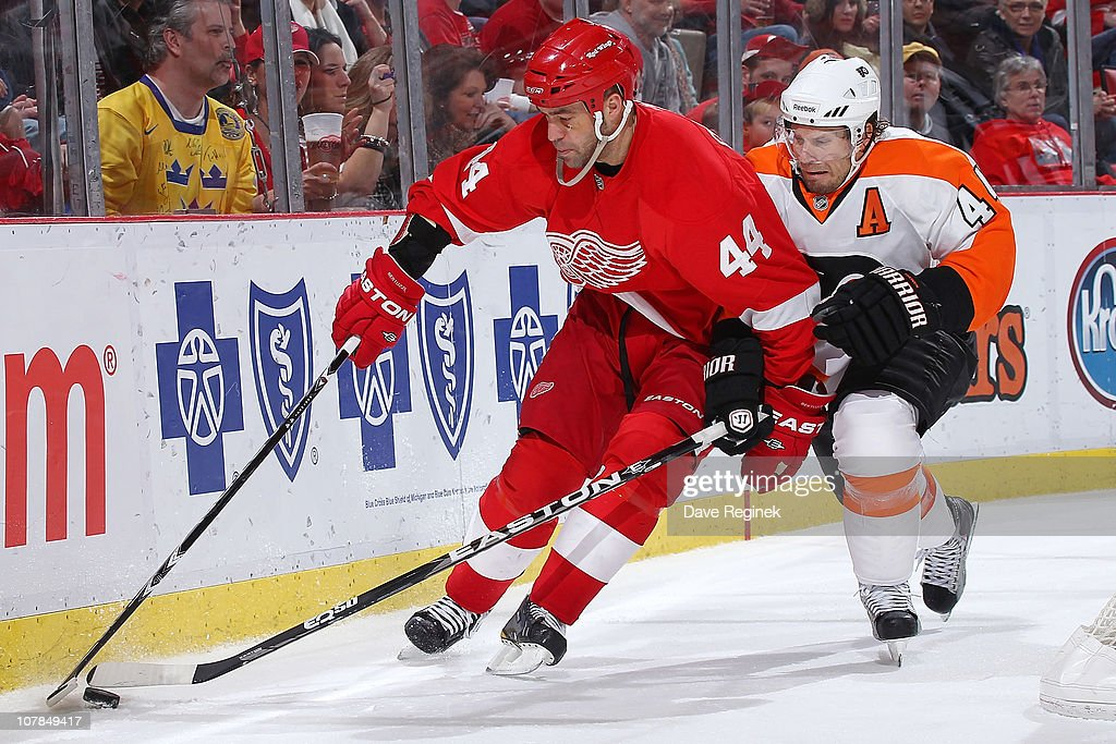 Todd Bertuzzi #44 of the Detroit Red Wings Carries the puck along the boards while Kimmo Timonen #44 battles for controll during an NHL game at Joe Louis Arena on January 2, 2011 in Detroit, Michigan. Flyers beat Wings 3-2