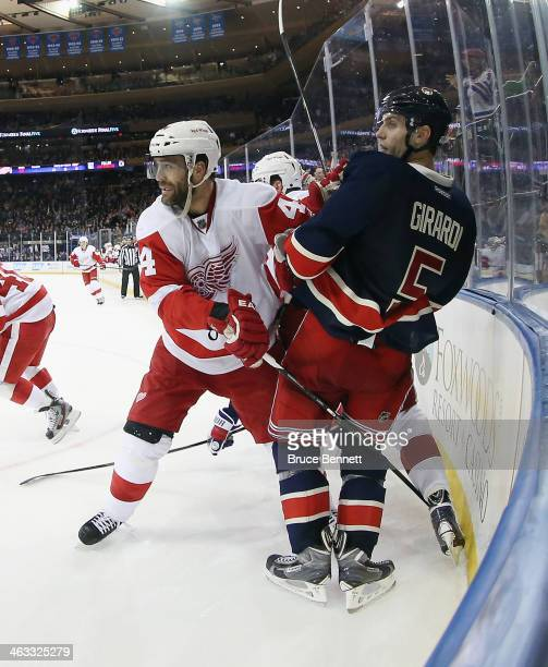 Todd Bertuzzi of the Detroit Red Wings checks Dan Girardi of the New York Rangers at Madison Square Garden on January 16 2014 in New York City The...