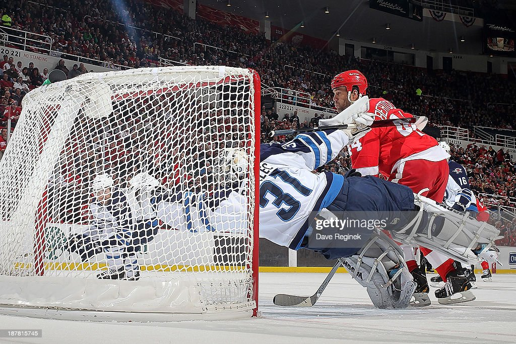 <a gi-track='captionPersonalityLinkClicked' href=/galleries/search?phrase=Todd+Bertuzzi&family=editorial&specificpeople=202476 ng-click='$event.stopPropagation()'>Todd Bertuzzi</a> #44 of the Detroit Red Wings posts in front of the net as Ondrej Pavelec #31 of the Winnipeg Jets dives but cannot save the Pavel Datsyuk #13 (not pictured) power-play goal during an NHL game at Joe Louis Arena on November 12, 2013 in Detroit, Michigan. Winnipeg Jets defeated the Detroit Red Wings 3-2 in a shootout
