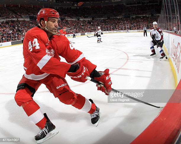 Todd Bertuzzi of the Detroit Red Wings reaches behind his body for the puck against defenseman Andre Benoit of the Colorado Avalanche during an NHL...