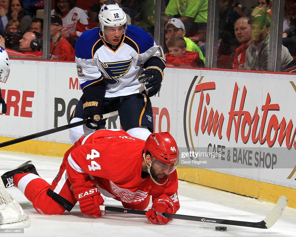 <a gi-track='captionPersonalityLinkClicked' href=/galleries/search?phrase=Todd+Bertuzzi&family=editorial&specificpeople=202476 ng-click='$event.stopPropagation()'>Todd Bertuzzi</a> #44 of the Detroit Red Wings tries to play the puck from his knees after being knocked down by <a gi-track='captionPersonalityLinkClicked' href=/galleries/search?phrase=Derek+Roy&family=editorial&specificpeople=203272 ng-click='$event.stopPropagation()'>Derek Roy</a> #12 of the St. Louis Blues during an NHL game on January 20, 2014 at Joe Louis Arena in Detroit, Michigan.