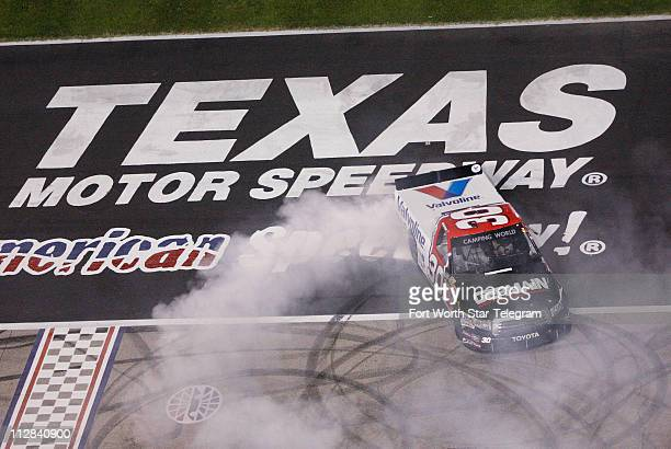 Todd Bodine burns his tires over the TMS logo after winning the NASCAR Camping World Truck Series Winstar World Casino 400K at Texas Motor Speedway...