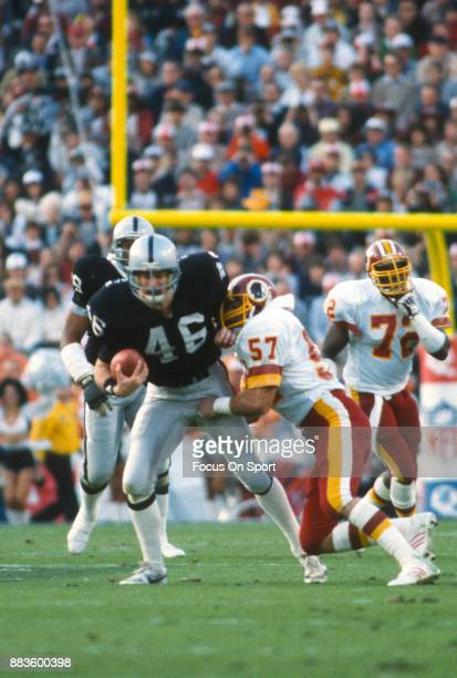 Todd Christensen of the Los Angeles Raiders fights off the tackle of Rich Milot of the Washington Redskins during Super Bowl XVIII on January 22 1984...