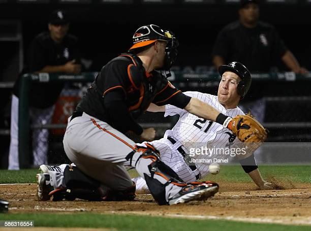 Todd Frazier of the Chicago White Sox slides in to score a run in the 4th inning as Matt Wieters of the Baltimore Orioles drops the ball at US...