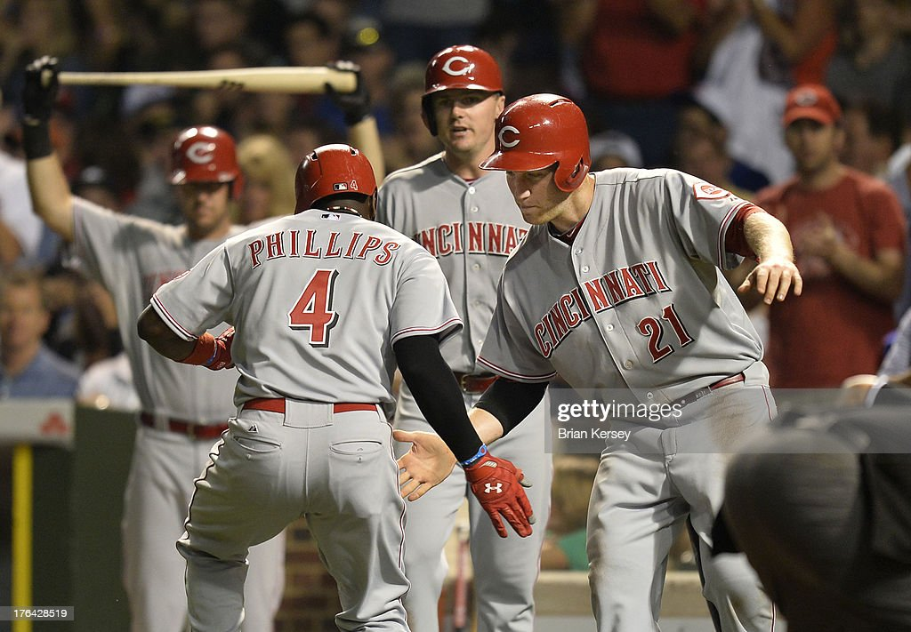 <a gi-track='captionPersonalityLinkClicked' href=/galleries/search?phrase=Todd+Frazier&family=editorial&specificpeople=4778756 ng-click='$event.stopPropagation()'>Todd Frazier</a> #21 of the Cincinnati Reds (R) congratulates Brandon Phillips #4 at home plate after Phillips hit a two-run home run scoring Frazier during the seventh inning against the Chicago Cubs at Wrigley Field on August 12, 2013 in Chicago, Illinois.