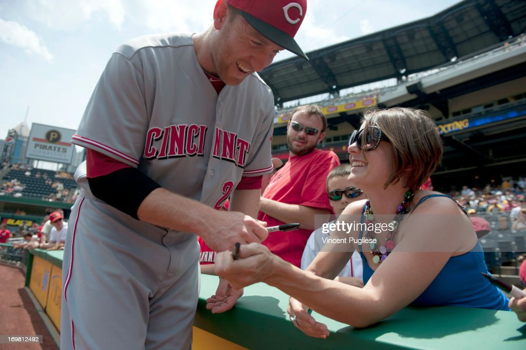 Todd Frazier #21 of the Cincinnati Reds signs an autograph for Natalie Ball of Columbus, Ohio, prior to their game against the Pittsburgh Pirates at PNC Park on June 2, 2013 in Pittsburgh, Pennsylvania.