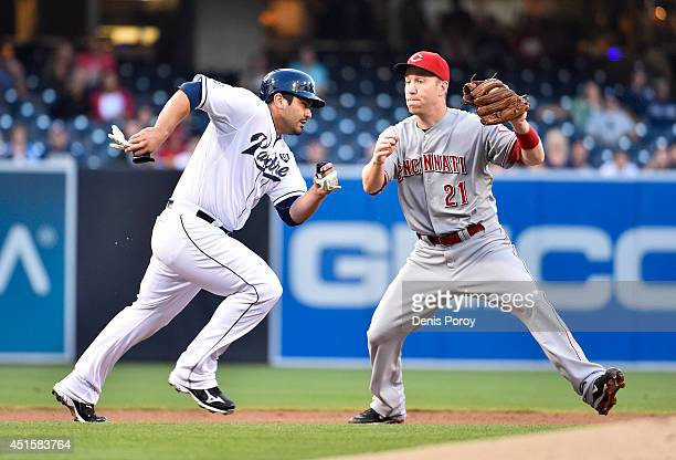 Todd Frazier of the Cincinnati Reds tags out Carlos Quentin of the San Diego Padres as he's caught off second base during the first inning of a...