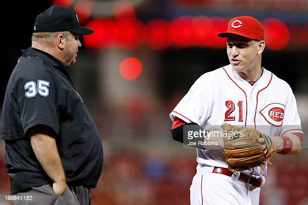 Todd Frazier of the Cincinnati Reds talks with third base umpire Wally Bell during the game against the Philadelphia Phillies at Great American Ball...