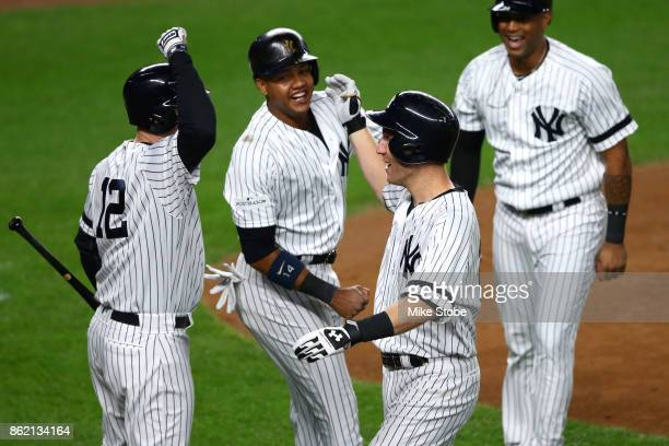 Todd Frazier of the New York Yankees celebrates hitting a 3run home run with teammates Chase Headley and Starlin Castro against the Houston Astros...