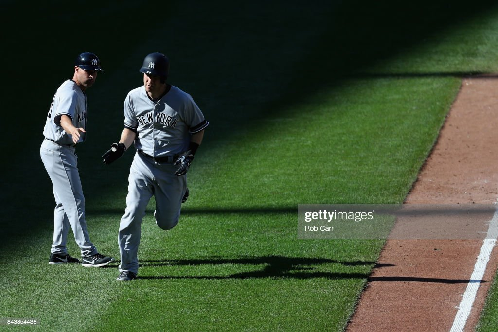 Todd Frazier #29 of the New York Yankees is congratulated by third base coach Joe Espada #53 after hitting a solo home run against the Baltimore Orioles in the seventh inning at Oriole Park at Camden Yards on September 7, 2017 in Baltimore, Maryland.