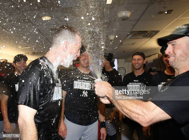 Todd Frazier of the New York Yankees is sprayed by Brett Gardner as they celebrate their playoffclinching victory during MLB game action against the...