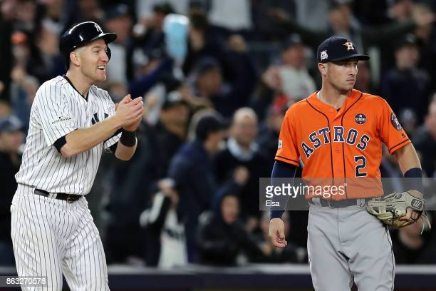 Todd Frazier of the New York Yankees reacts after a advancing to third base in the eighth inning as Alex Bregman of the Houston Astros looks on...