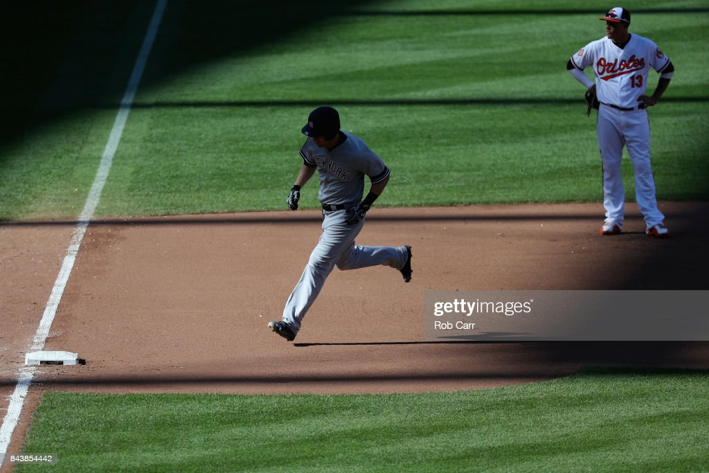 Todd Frazier #29 of the New York Yankees rounds the bases in front of Manny Machado #13 of the Baltimore Orioles after hitting a solo home run in the seventh inning at Oriole Park at Camden Yards on September 7, 2017 in Baltimore, Maryland.