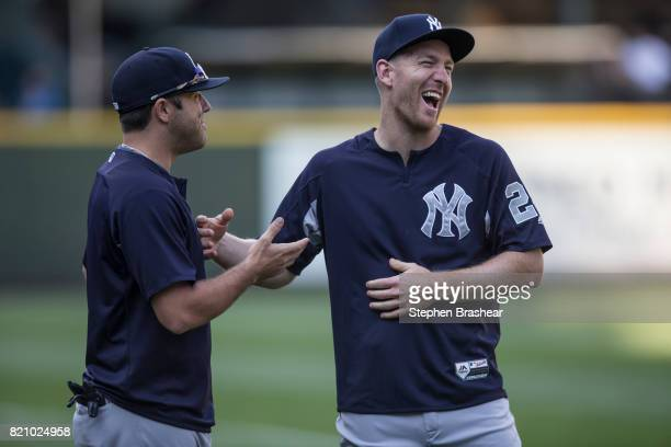 Todd Frazier right of the New York Yankees jokes with Austin Romine of the New York Yankees on the field before a game against the Seattle Mariners...