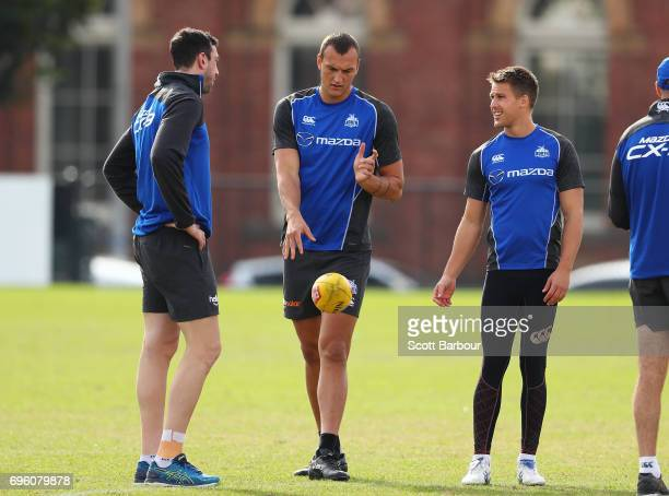 Todd Goldstein Braydon Preuss and Andrew Swallow of the Kangaroos talk during a North Melbourne Kangaroos AFL training session at Arden Street Ground...