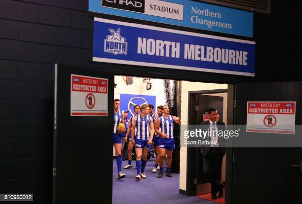 Todd Goldstein of the Kangaroos and Jack Ziebell of the Kangaroos lead the Kangaroos as they leave their changing rooms to run onto the field during...