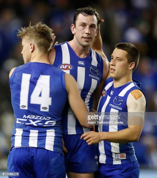 Todd Goldstein of the Kangaroos is consoled by teammates Trent Dumont and Nathan Hrovat of the Kangaroos after missing a shot at goal to win the game...