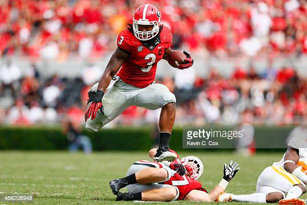 Todd Gurley of the Georgia Bulldogs leaps over Taylor Maxey as he rushes against the Tennessee Volunteers at Sanford Stadium on September 27 2014 in...