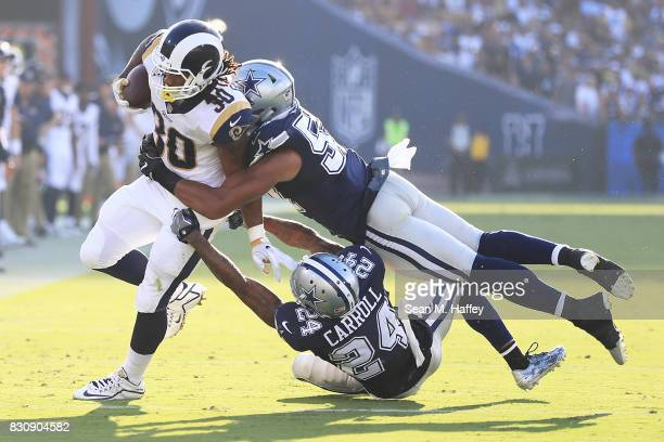 Todd Gurley of the Los Angeles Rams gets tackled by Damien Wilson and Nolan Carroll of the Dallas Cowboys during the preseason game against the...