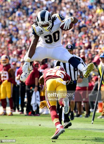 Todd Gurley of the Los Angeles Rams hurdles over Bashaud Breeland of the Washington Redskins on his way to scoring a touchdown at Los Angeles...