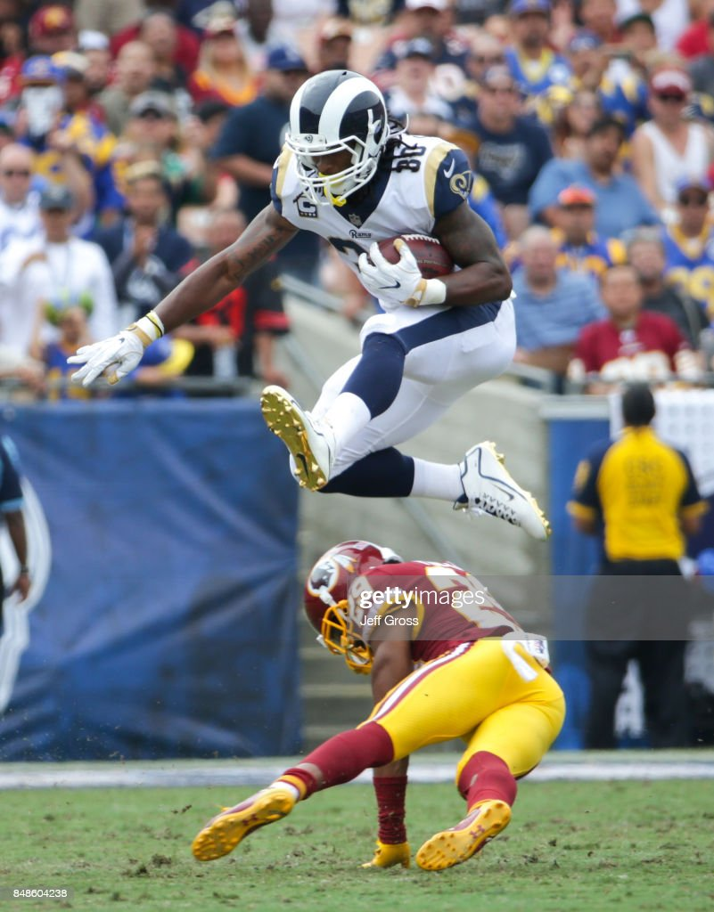 Todd Gurley #30 of the Los Angeles Rams leaps over Kendall Fuller #29 of the Washington Redskins at Los Angeles Memorial Coliseum on September 17, 2017 in Los Angeles, California.