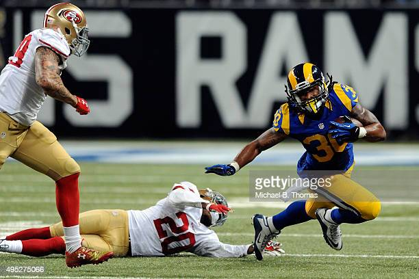 Todd Gurley of the St Louis Rams carries the ball fater fending off a tackle attempt from Kenneth Acker of the San Francisco 49ers in the third...