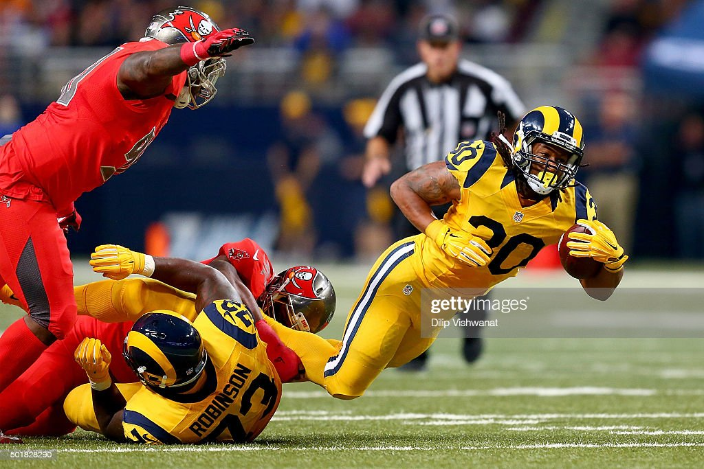 Todd Gurley #30 of the St. Louis Rams is tripped up as he carries the ball in the second quarter against the Tampa Bay Buccaneers at the Edward Jones Dome on December 17, 2015 in St. Louis, Missouri.