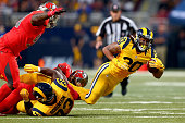 Todd Gurley of the St Louis Rams is tripped up as he carries the ball in the second quarter against the Tampa Bay Buccaneers at the Edward Jones Dome...