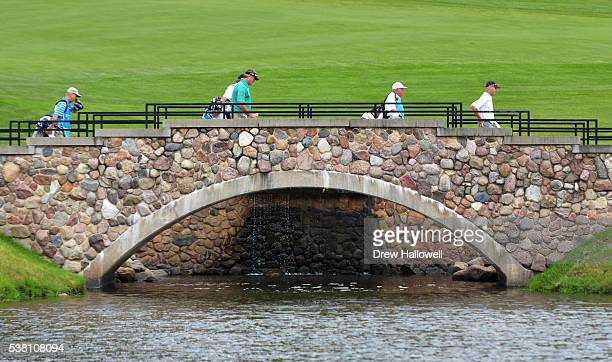 Todd Hamilton and Gary Hallberg cross a bridge to the 18th fairway during the second round of the Principal Charity Classic at the Wakonda Club on...