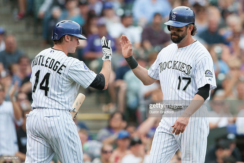 <a gi-track='captionPersonalityLinkClicked' href=/galleries/search?phrase=Todd+Helton&family=editorial&specificpeople=200735 ng-click='$event.stopPropagation()'>Todd Helton</a> #17 of the Colorado Rockies celebrates a fourth inning run with <a gi-track='captionPersonalityLinkClicked' href=/galleries/search?phrase=Josh+Rutledge&family=editorial&specificpeople=9541486 ng-click='$event.stopPropagation()'>Josh Rutledge</a> #14 during a game against the Arizona Diamondbacks at Coors Field on September 22, 2013 in Denver, Colorado.