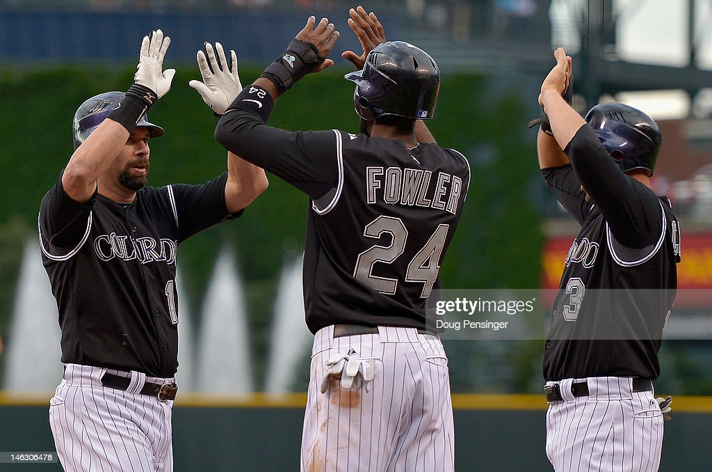 <a gi-track='captionPersonalityLinkClicked' href=/galleries/search?phrase=Todd+Helton&family=editorial&specificpeople=200735 ng-click='$event.stopPropagation()'>Todd Helton</a> #17 of the Colorado Rockies celebrates his first inning grand slam off of Tommy Milone #57 of the Oakland Athletics with <a gi-track='captionPersonalityLinkClicked' href=/galleries/search?phrase=Dexter+Fowler&family=editorial&specificpeople=4949024 ng-click='$event.stopPropagation()'>Dexter Fowler</a> #24 and <a gi-track='captionPersonalityLinkClicked' href=/galleries/search?phrase=Michael+Cuddyer&family=editorial&specificpeople=208127 ng-click='$event.stopPropagation()'>Michael Cuddyer</a> #3 of the Colorado Rockies who scored on the play as they Rockies took a 5-2 lead in the first inning during Interleague Play at Coors Field on June 13, 2012 in Denver, Colorado.