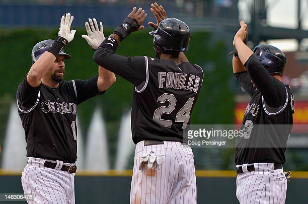 Todd Helton of the Colorado Rockies celebrates his first inning grand slam off of Tommy Milone of the Oakland Athletics with Dexter Fowler and...
